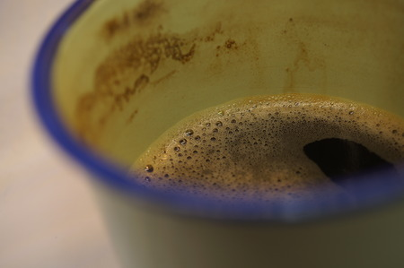 Macro close-up shot of nice coffee foam on the surface of a strong black coffee in a geen and blue cup