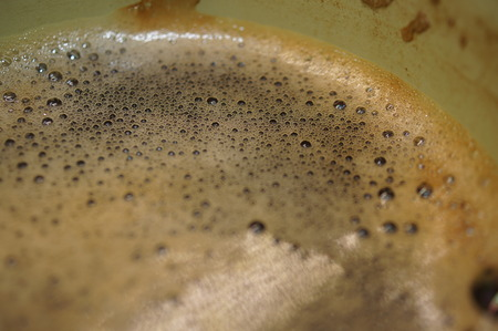 Macro close-up shot of nice coffee foam on the surface of a strong black coffee in a geen cup