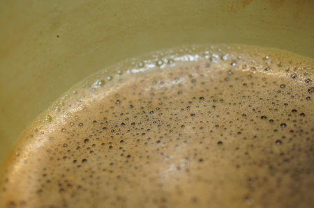 Black Coffee Close-up in a green pewter cup (Detail Macro shot)