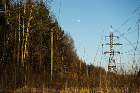 a line of high-voltage pillars through a plowed agricultural field, a forest on the horizon and a blue sky