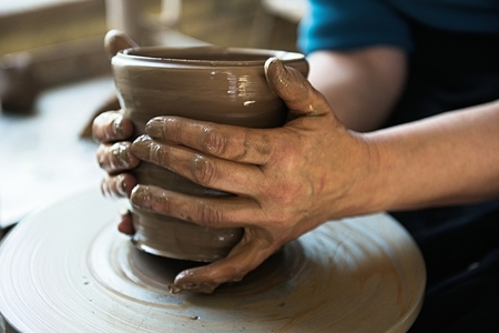 A lace maker and ceramicist create artwork. Hands top view