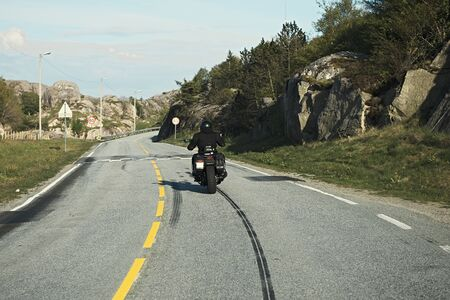 back view of two motorcyclists on mountain road