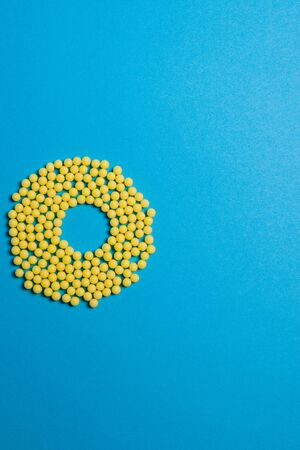 Yellow medical pills on blue background with copy space for text. Alternative homeopathy medicine, healthcare and wellness concept. Selective focus