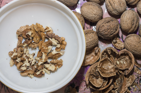 Walnuts, whole and crushed on a wooden table.