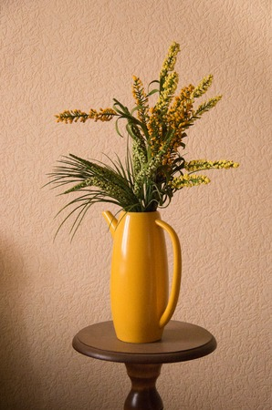 Decorative flowers for home interior in a yellow jug teapot 免版税图像