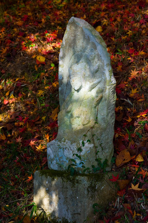 Stone Buddha surrounded by fallen leaves Stock Photo