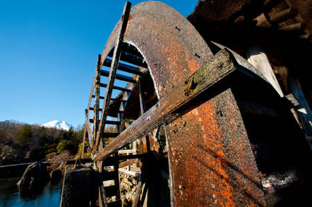 A long-used rusted water mill with Mt. Fuji