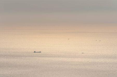 A ship sailing the sparkling sea in the morning sun