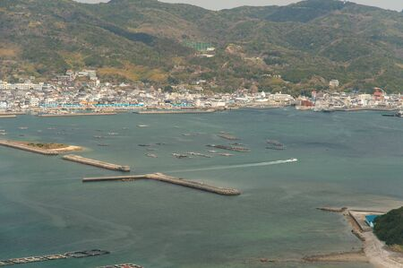 A ship sailing in the Seto Inland Sea, lined with farmed salmon