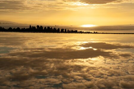Beautiful sunrise and clouds in the water puddle Stok Fotoğraf