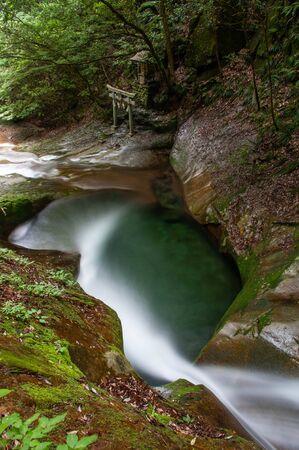 Mountain stream flow with shrine