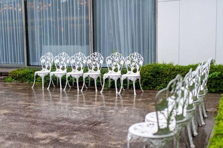 Fashionable white chair wet in the rain