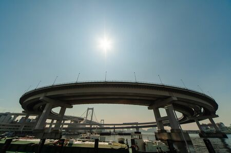 A huge bridge with a beautiful curve and the sun