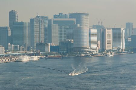 A ship sailing in front of the buildings in Tokyo 写真素材