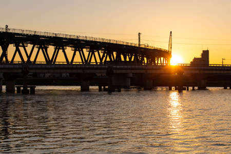 A railway bridge under construction, a sunset and a huge river