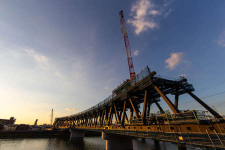A steel bridge under construction, sunset and clouds