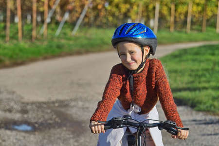 girl having fun riding her bicycle in wineyards photo