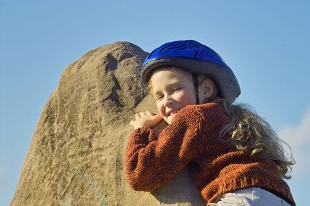 affraid: little girl climbing and reaching the top of the rock