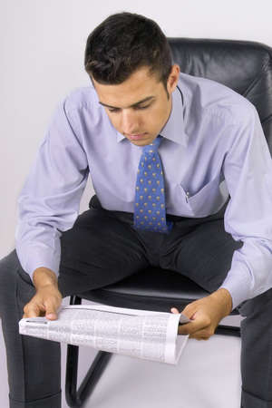 attractive young business man reading the newspaper photo