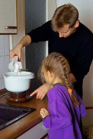 licking finger: little girl cooking together with her father Stock Photo
