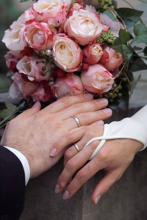 hands of the bride and groom with flowers Stock Photo