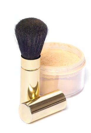 powder brush in golden case with loose powder