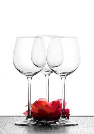 three wine glasses in backlight with red flower photo