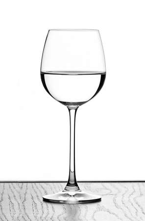 one wine glass in backlight on white contrast background