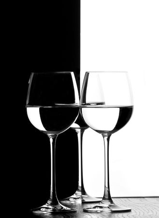 three wine glasses in backlight on the black and white contrast background Stock Photo