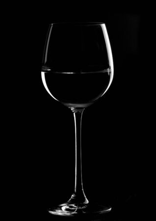 and backlight: one wine glasses in backlight on the black  contrast background Stock Photo