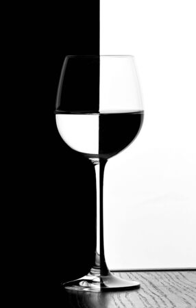 isoliert: one wine glass in backlight on the black and white contrast background with domino effect