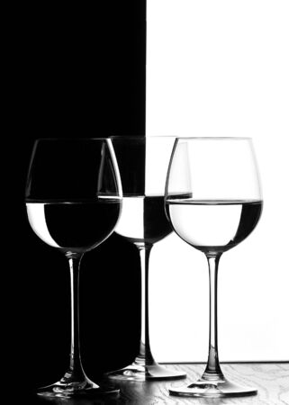 isoliert: three wine glasses in backlight on the black and white contrast background Stock Photo