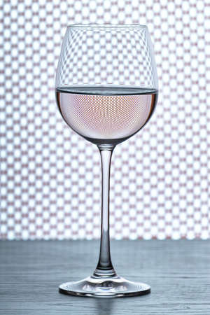 isoliert: one wine glass in backlight on contrast background over grid fish net