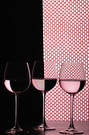 three wine glasses in backlight on the black and white contrast background with red grid fish net