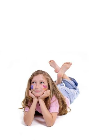beautiful young girl with a flower and butterfl drawing on her cheek laying on the floor looking up