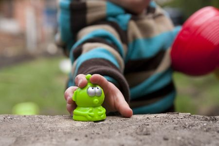 Close up of toddlers hand grabbing for a green plastic alien Banco de Imagens