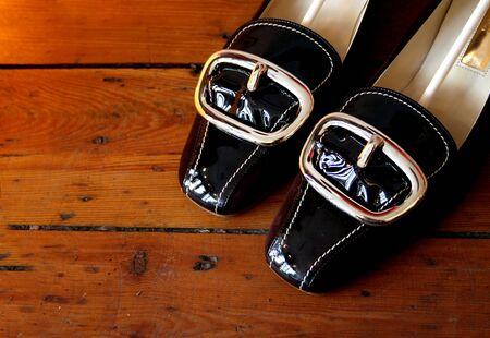 unworn: Pair of black patent leather shoes on wooden floor