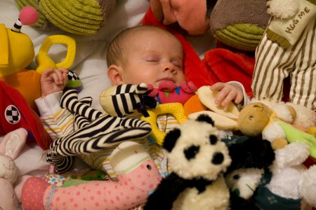 Baby Asleep in pile of Brightly coloured cuddly toys photo