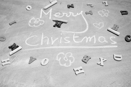 writing merry christmas and drawing heart,flower with chalk, plastic letter, wood board