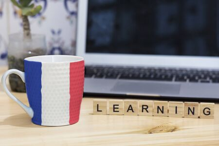 コーヒー カップ、手紙木製学習、灰色のノート パソコンにフランスの国旗が描かれました。