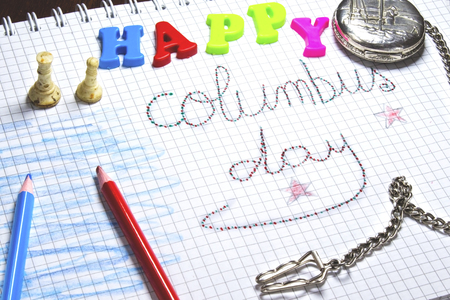 handwriting columbus day on notebook, silver pocket watch,red and blue pen,beige chess,colorful happy letter Archivio Fotografico