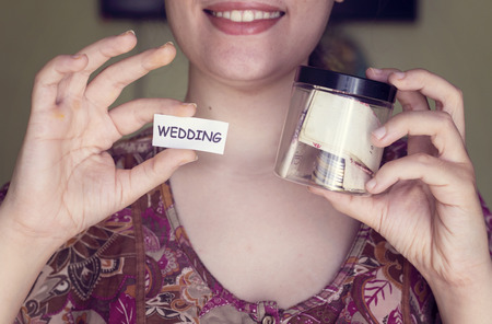 algeria: Algerian woman with beautiful smile hold a plastic pot and wedding paper and saving money for wedding Stock Photo