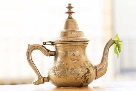 arabic antique old silver teapot,fresh green mint on wood table Stock Photo