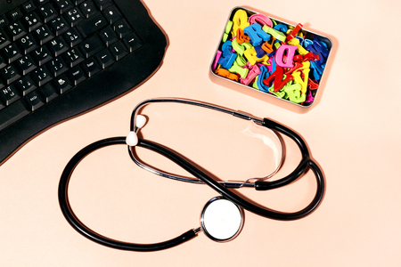 black keyboard and stethoscope, colorful letters in metal box Stock Photo