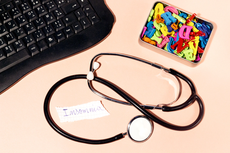 insomnia written in paper,black keyboard and stethoscope, colorful letters in metal box