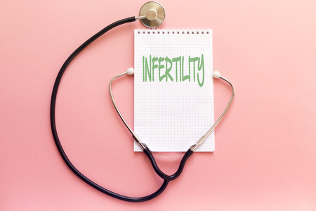 disease infertility concept handwriting on white notebook and stethoscope on pink background