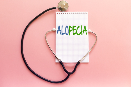 disease alopecia concept handwriting on white notebook and stethoscope on pink background