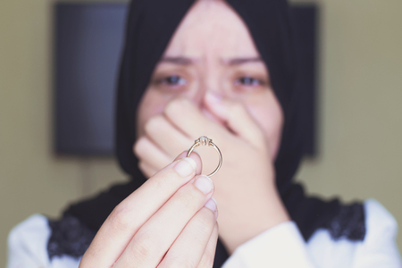 beautiful muslim woman crying and  returning wedding ring to her husband