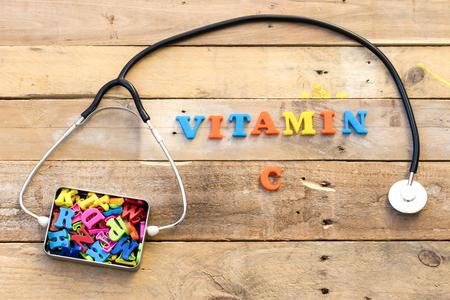 概念ビタミン、心臓聴診器および金属箱のカラフルな手紙