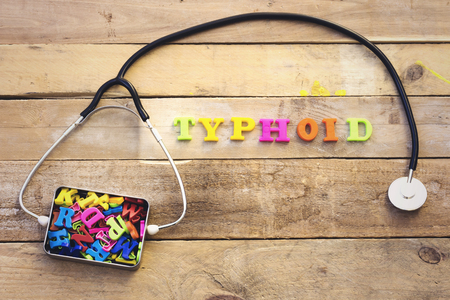 Concept typhoid, heart stethoscope and colorful letters in metal box Stock Photo